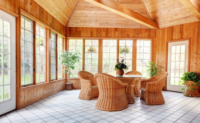 Wooden wall sun room interior with wicker furniture